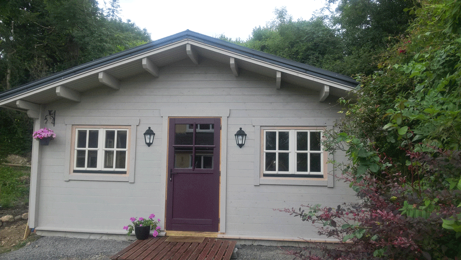 Limerick Log Cabin by Timber Living of  front view of doors and windows surrounded all by trees