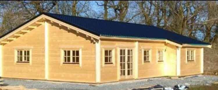 Youghal Log Cabin by Timber Living of  front view of the large spacious log cabin settled in the autumn trees