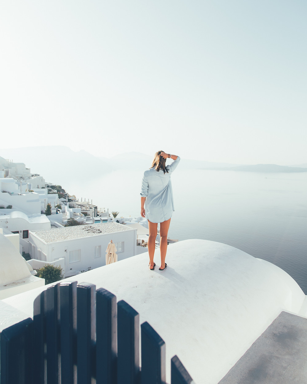 White woman standing on top of a house in Greece overlooking the ocean