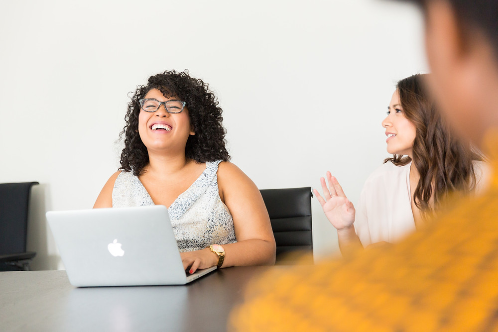 Latinx woman laughing in a meeting with her colleagues while on her laptop