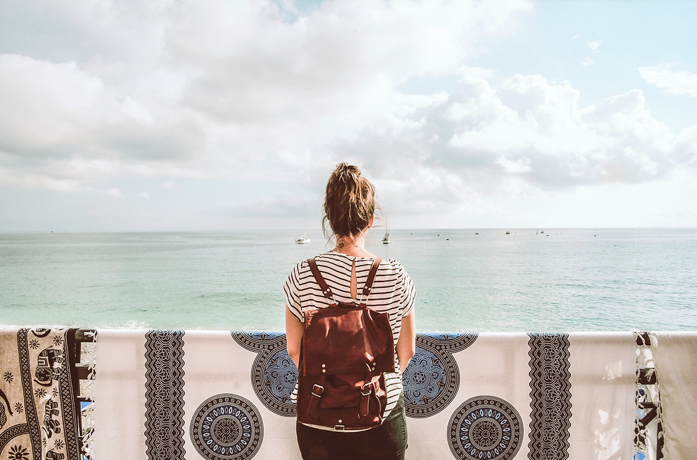 Girl staring out into the open ocean with a backpack on her back