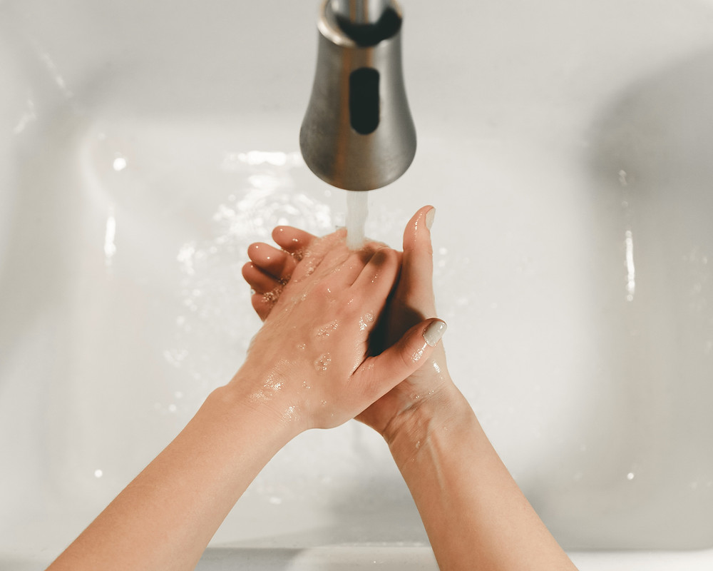 Woman washing her hands over a white sink