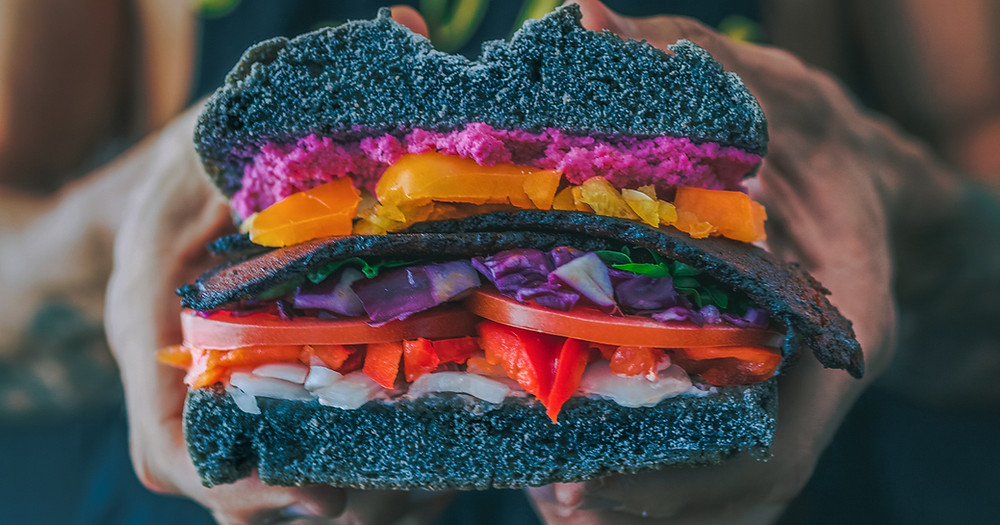 Woman holding a colorful vegan sandwich up to the camera