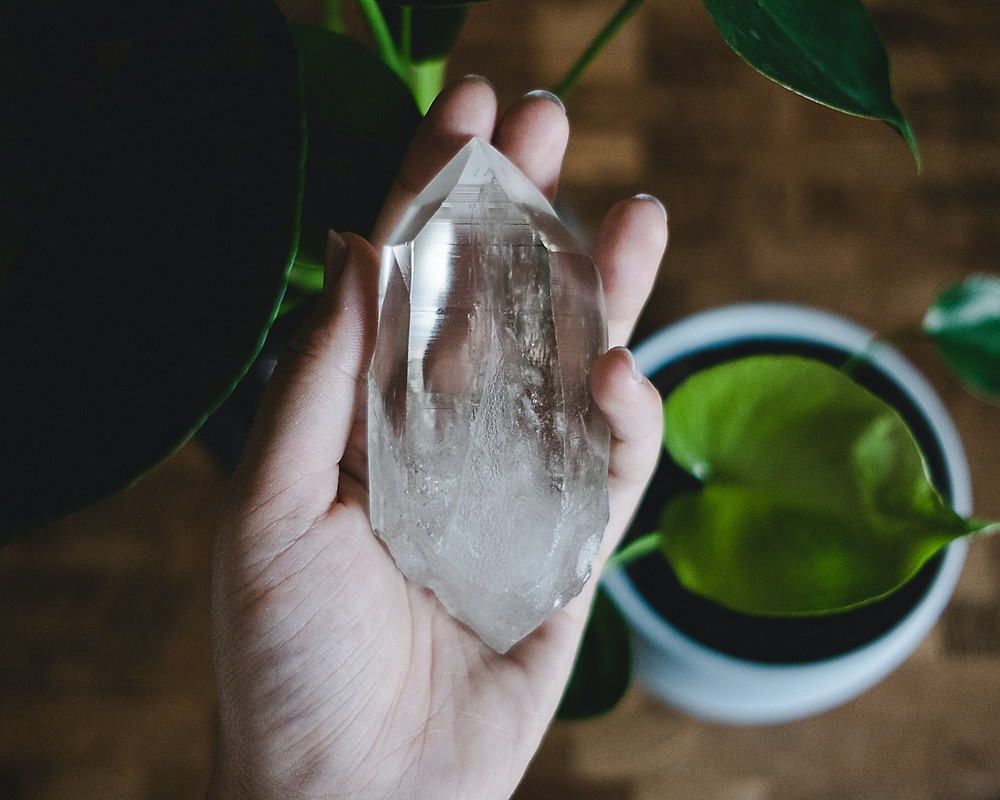 Woman holding a clear quartz crystal in her hand