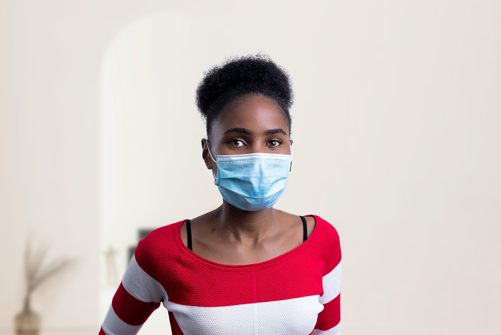 Black woman wearing a surgical face mask in her home