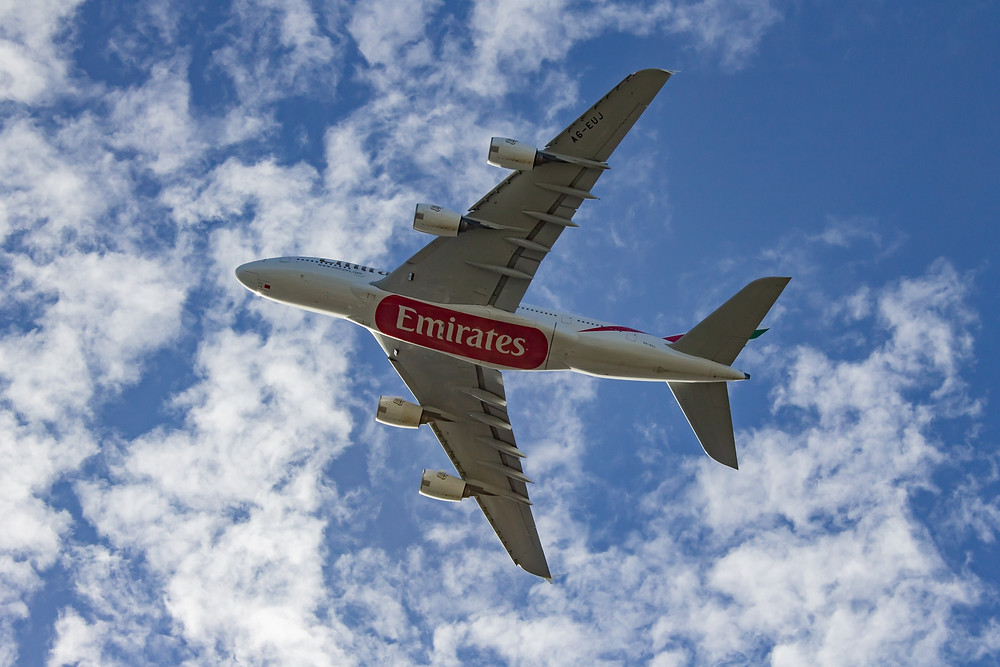 Emirates airplane flying in the blue cloudy sky
