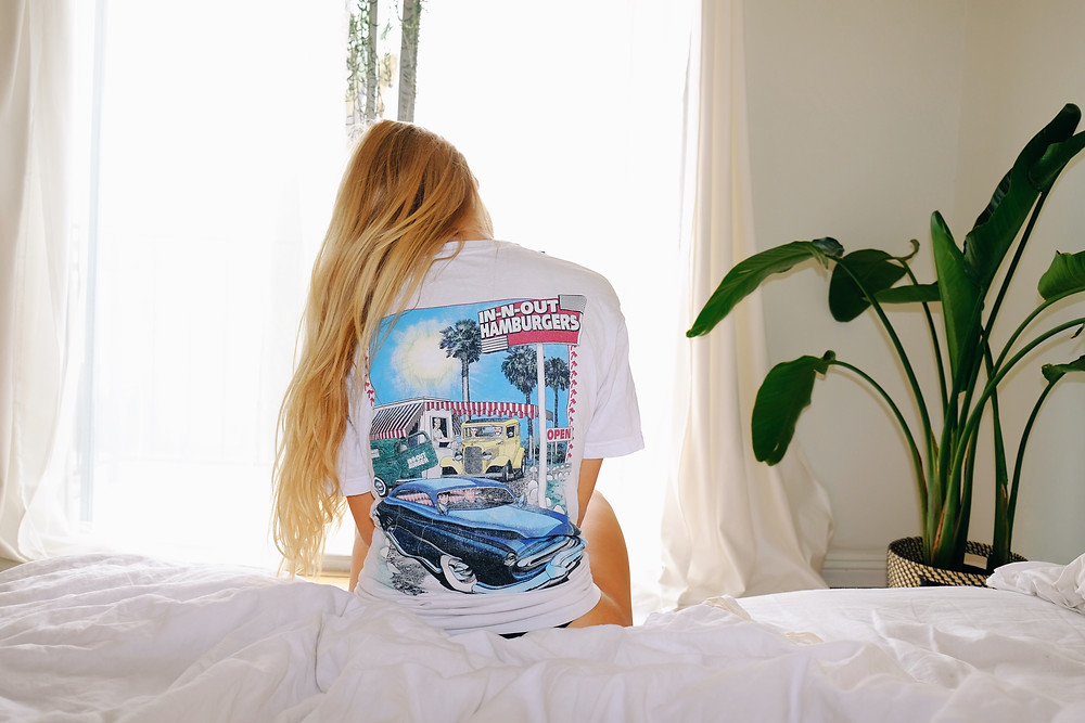 woman in white and blue crew neck t-shirt sitting on bed