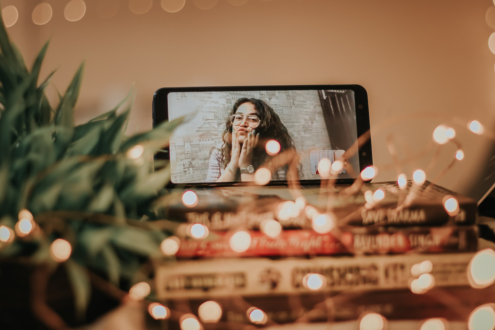 Girl on FaceTime on iPhone stacked on top of books and surrounded by string lights