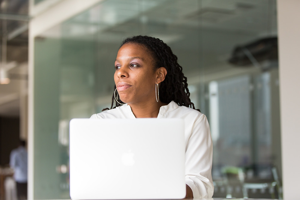 Black woman on her laptop in an office while looking out the window at something out of frame