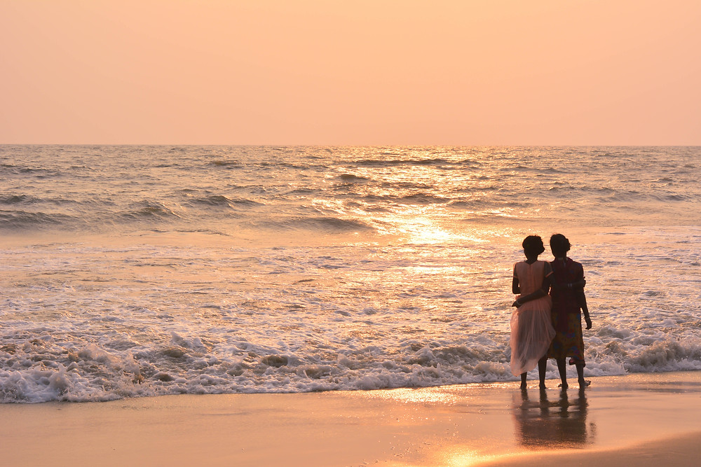 Two people standing at the edge of the water watching the sun set at the beach