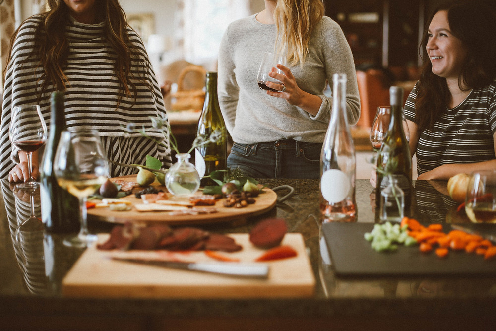 Women gathered around a table enjoying wine and small bites