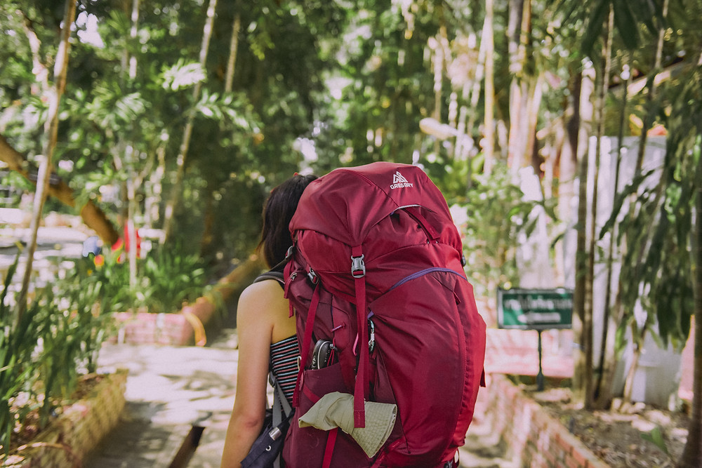Woman carrying a big red backpack on her back while traveling