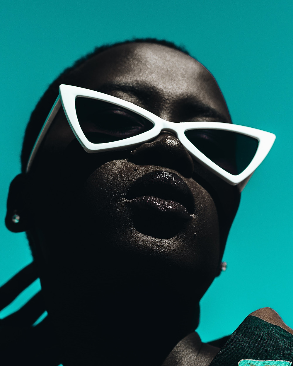 Dark-skinned Black girl wearing white-trimmed sunglasses in front of a teal background