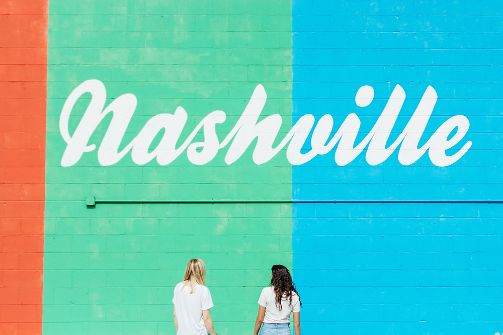 "Two white women standing in front of a multi-colored wall that has the words ""Nashville"" on it in cursive"