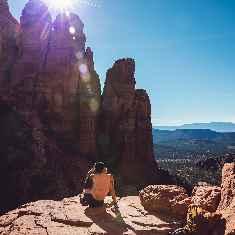 Woman sitting on edge of red rock after climbing up it in Sedona