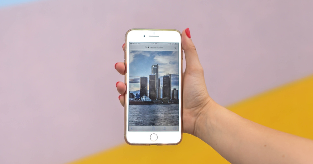 Woman holding up phone in front of pink and yellow painted wall with a picture of a skyline on it