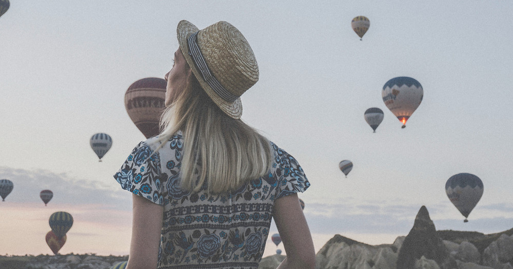 Blonde-haired woman wearing a straw hat and looking up at hot hair balloons in the desert