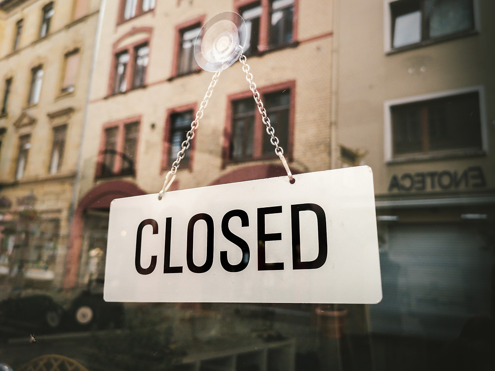 "Black and white ""closed"" sign hanging in a storefront window"