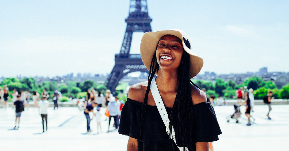 Black woman wearing a tan sun hat and black off-the-shoulder dress smiling while posing in front of the Eiffel Tower in Paris, France
