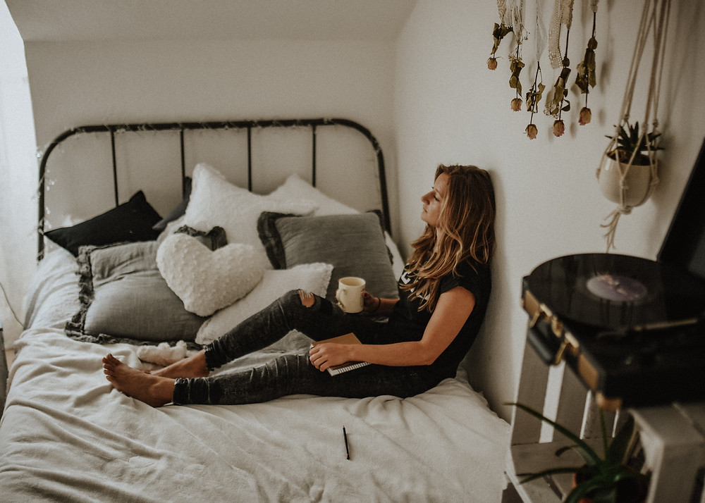 girl sitting on bed while holding a cup of coffee and a journal