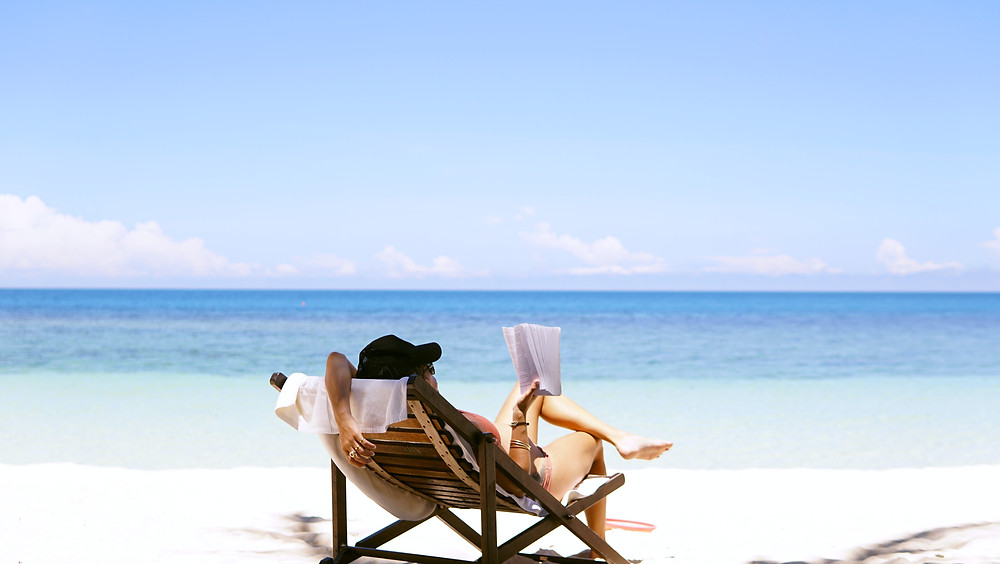 White woman lounging in a beach chair while reading a book on the shore