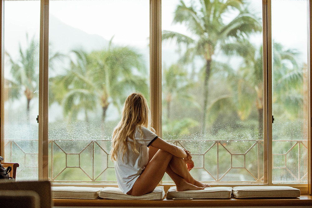 White woman sitting on white cushion near glass window with palm trees in the distance