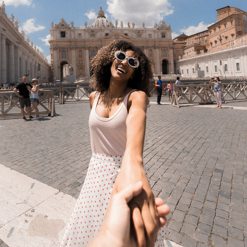 Black curly haired woman smiling while holding the hand of her significant other for a travel photo