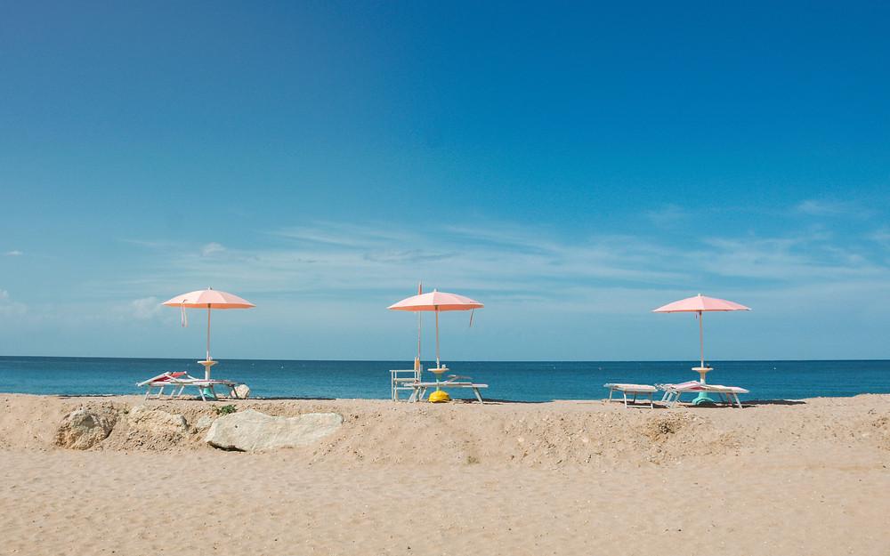 Beach chairs and umbrellas six feet apart on the shore of a beach