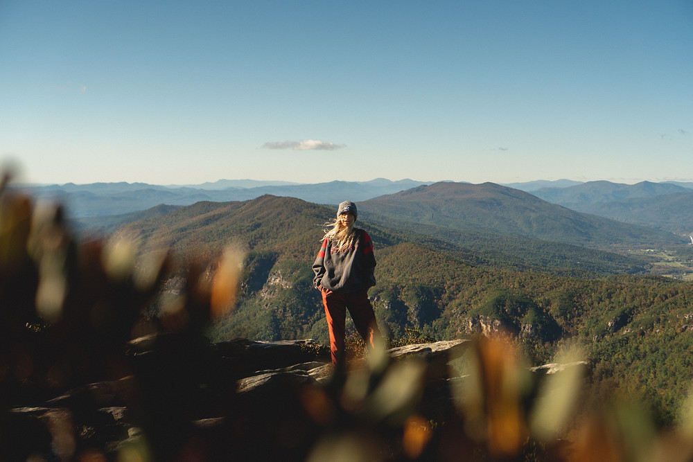 White blonde girl standing on top of a cliff overlooking a mountain landscape in North Carolina during the fall