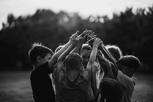 kids-standing-in-circle-with-hands-raise