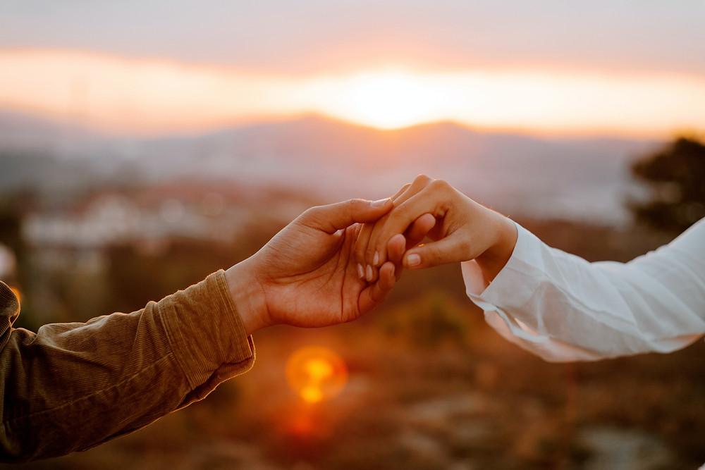 Hände halten vor Sonnenuntergang
