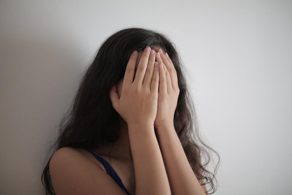 Frau mit Händen vorm Gesicht