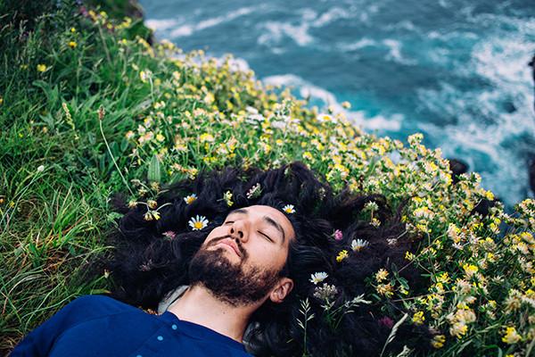 Mann liegt auf einer Blumenwiese an einem Klippenrand