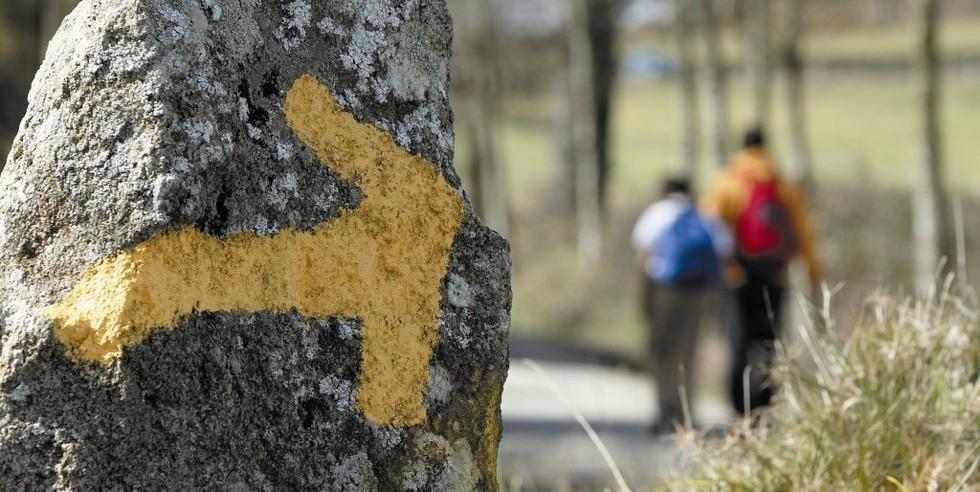 Flecha amarilla señalando el camino pintada en una roca del camino