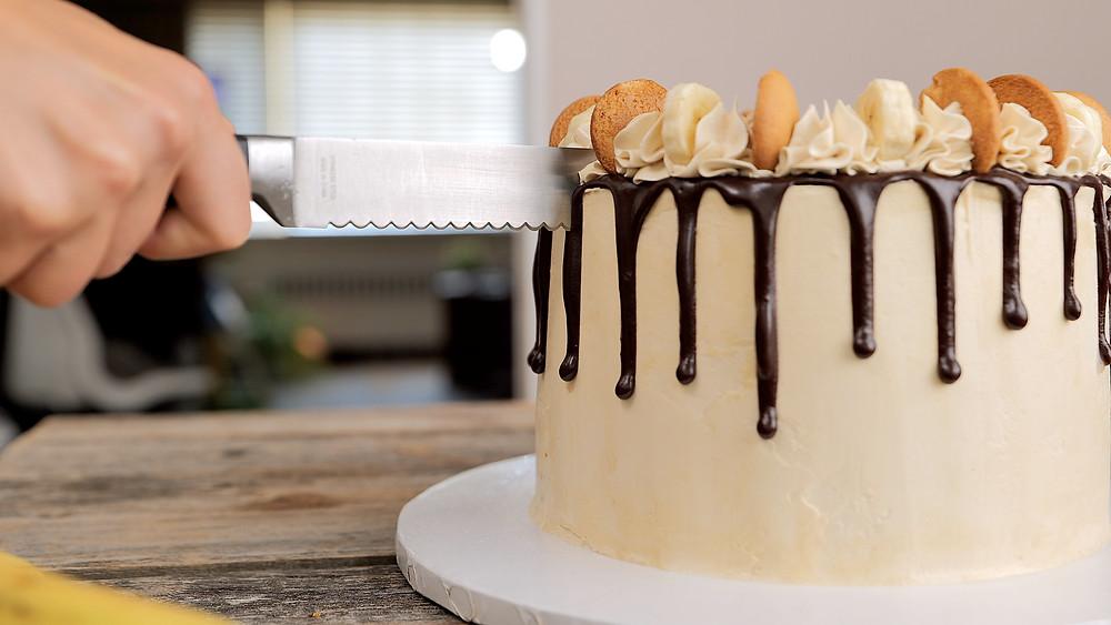 cutting the decorated banana pudding cake