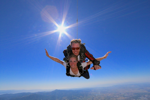Tandem instructor and first time skydiver falling in clear blue skies with Sierra Nevadas in background