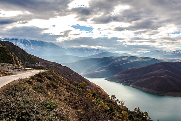 Winding mountain road above a large river