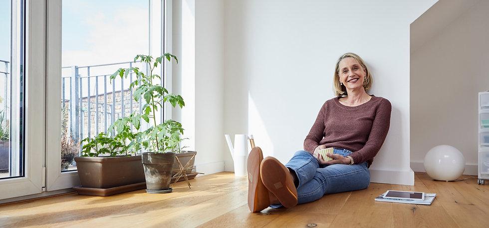 Mature woman sitting on floor with tea