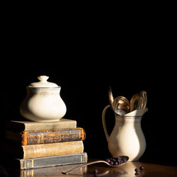 China creamer filled with teaspoons beside stack of books with sugar bowl on top