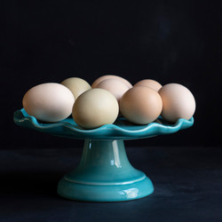 Fresh, organic eggs on a teal cake plate on a black background