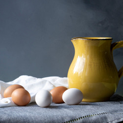 Yellow pitcher and tea towels with brown and white eggs