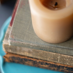 Soy candle sitting on vintage books