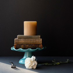 Soy candle on stack of vintage books on teal cake stand