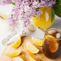 Iced tea in mason jar with cut lemons and pitcher holding lilacs