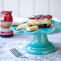 Raspberry cheesecake on teal cake stand with jar of jam in background and fork in foreground