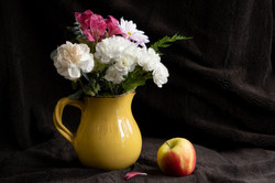 Yellow pitcher holding carnations with apple beside