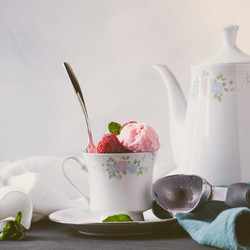 Strawberry ice cream in a china tea cup with teapot in background