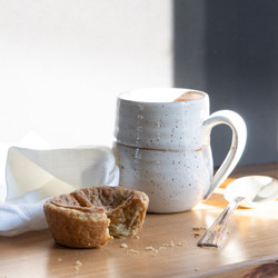 Pottery mug with tea and a butter tart in morning light