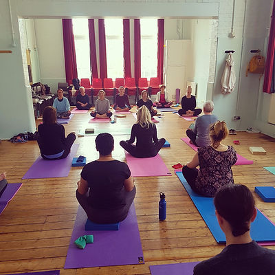 People sitting on mats in yoga class