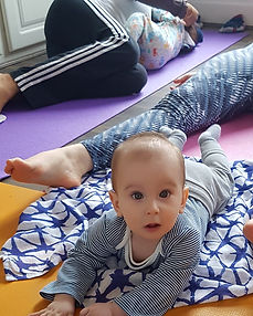 Close up of baby with adults practising yoga in background